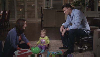 A screenshot from the TV show Bones: The characters of Booth, Brennan, and Christine, enjoy playtime at home.