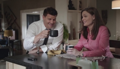 A screencap from the tv show Bones: the characters of Booth and Brennan look happy while enjoying coffee.