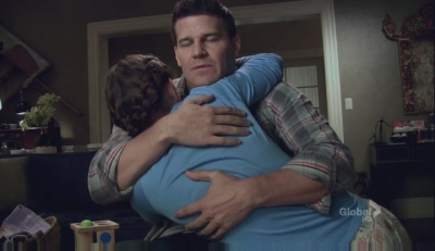 A screencap from the tv show Bones: The Characters of Booth and Brennan hug sweetly.