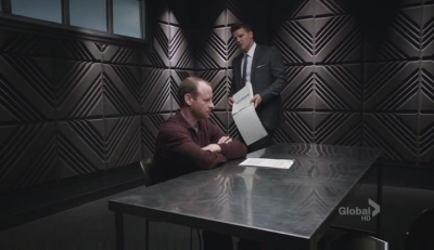 A screencap from the tv show Bones: the character of Dr. Craig sits in a dark room being interrogated by the character Booth.
