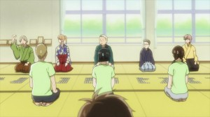 Students kneel in rows playing karuta, a card game
