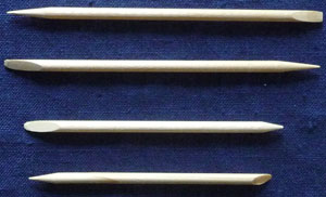 photo of 4 wooden orange sticks against a navy blue background