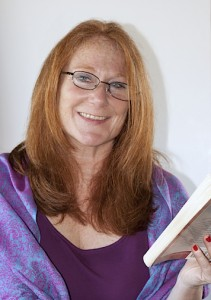 The author, smiling and holding a book