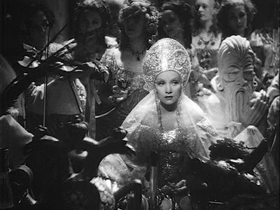 Still from The Scarlet Empress of Marlene Dietrich as Catherine the Great, in an elaborate gown and headdress, surrounded by musicians