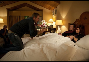 Adam and Kristina, in bed, receiving direction from Dax