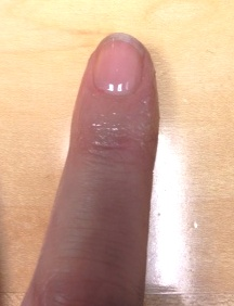 photo of Kym's finger with lip balm shininess and base coat of nail polish