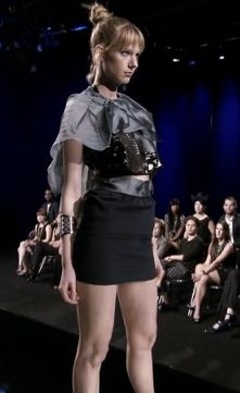 Emily's shredded mess: A black miniskirt and a shredded black top with a gray capelet