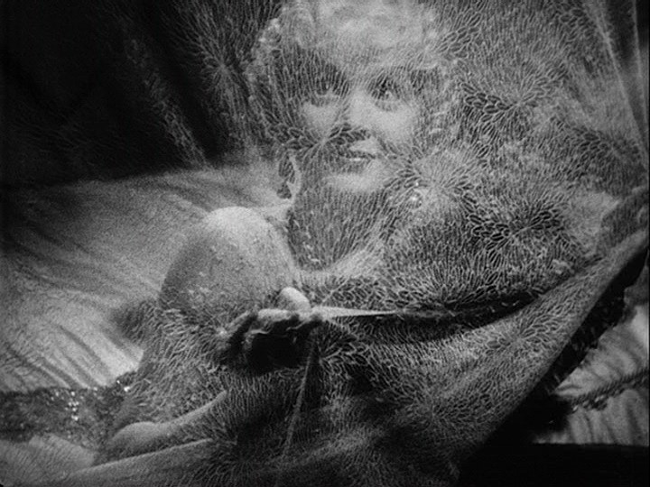 Still from The Scarlet Empress of Marlene Dietrich as Catherine the Great, peering through a gauzy curtain