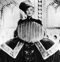 Still from The Scarlet Empress of Marlene Dietrich as Catherine the Great, wearing a dress with wide panniers and with her hands in a large fur muff