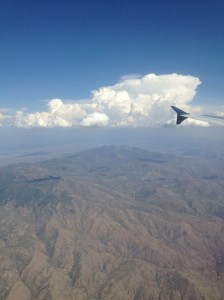 Photo taken out an airplane window of the mountains outside Los Angeles with a few puffy clouds in the sky.