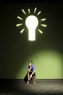 Man sitting under a large art installation of a glowing light bulb.