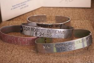Four metal POW/MIA bracelets