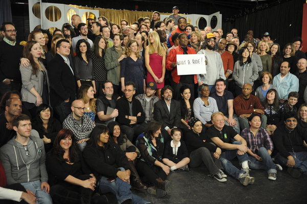 "Farewell photo of the cast and crew of 30 Rock; at center Tracy Jordan holds a sign that says ""What a ride!"""