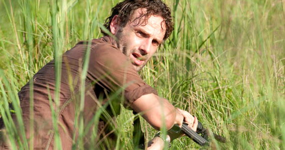 Rick, holding a gun while crouching in some tall grass