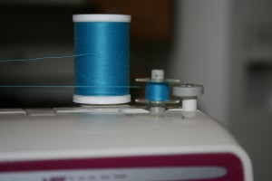 Picture of a sewing machine, spool of thread, and bobbin being wound.