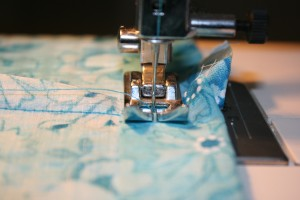Close-up picture of a sewing machine needle, sewing a hem.