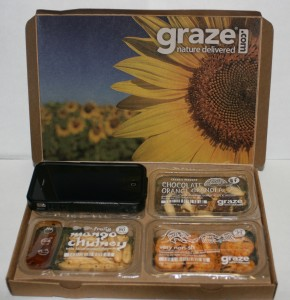 Picture of opened graze.com snack box with an iphone covering one snack item