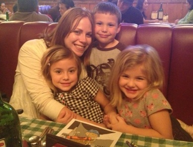 photo of Kym and her nieces and nephew inside a restaurant snuggled up in a booth