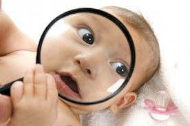 Baby with a magnifying glass up to his or her face