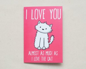 "Pink valentine card that says ""I love you almost as much as I love the cat,"" with a drawing of a white cat."