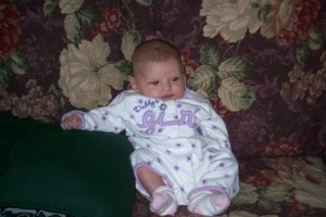 Bored looking baby slouched in a chair