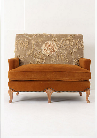 Sofa from Anthropologie with suede on the base, armrests, and seat cushion, and a rug that looks torn covering the back cushion.