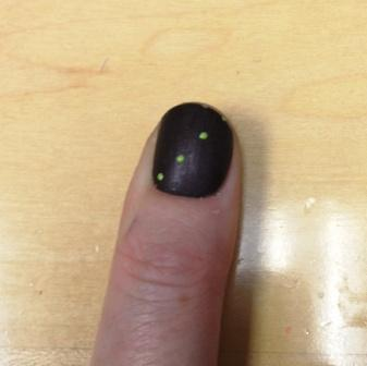 Photo of Kym's thumb with dark brown painted nail with a row of 4 green dots