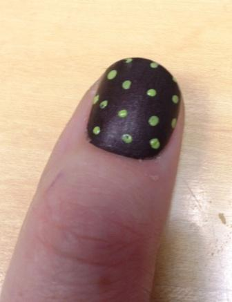 photo of kym's thumb painted dark brown with green polka dots