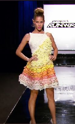 A dress with a white boatneck top and yellow ruffles cutting across the bodice, leading to a short skirt with yellow, orange, pink, and white ruffles