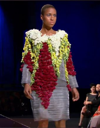 A really ugly shapeless gray dress with white, green, and red plants covering the bodice