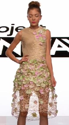 Dress matching the model's skintone with an overlay of green and pink leaves or petals, extending in a cage to her knees