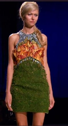 Dress with a moss skirt and orange petals on the bodice, with a silver neckpiece