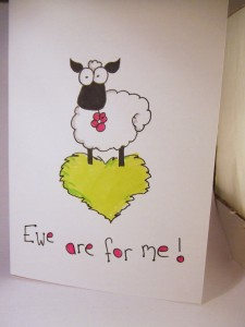 "Valentine card that has a drawing of a sheep on a heart-shaped patch of grass, captioned ""Ewe are for me."""
