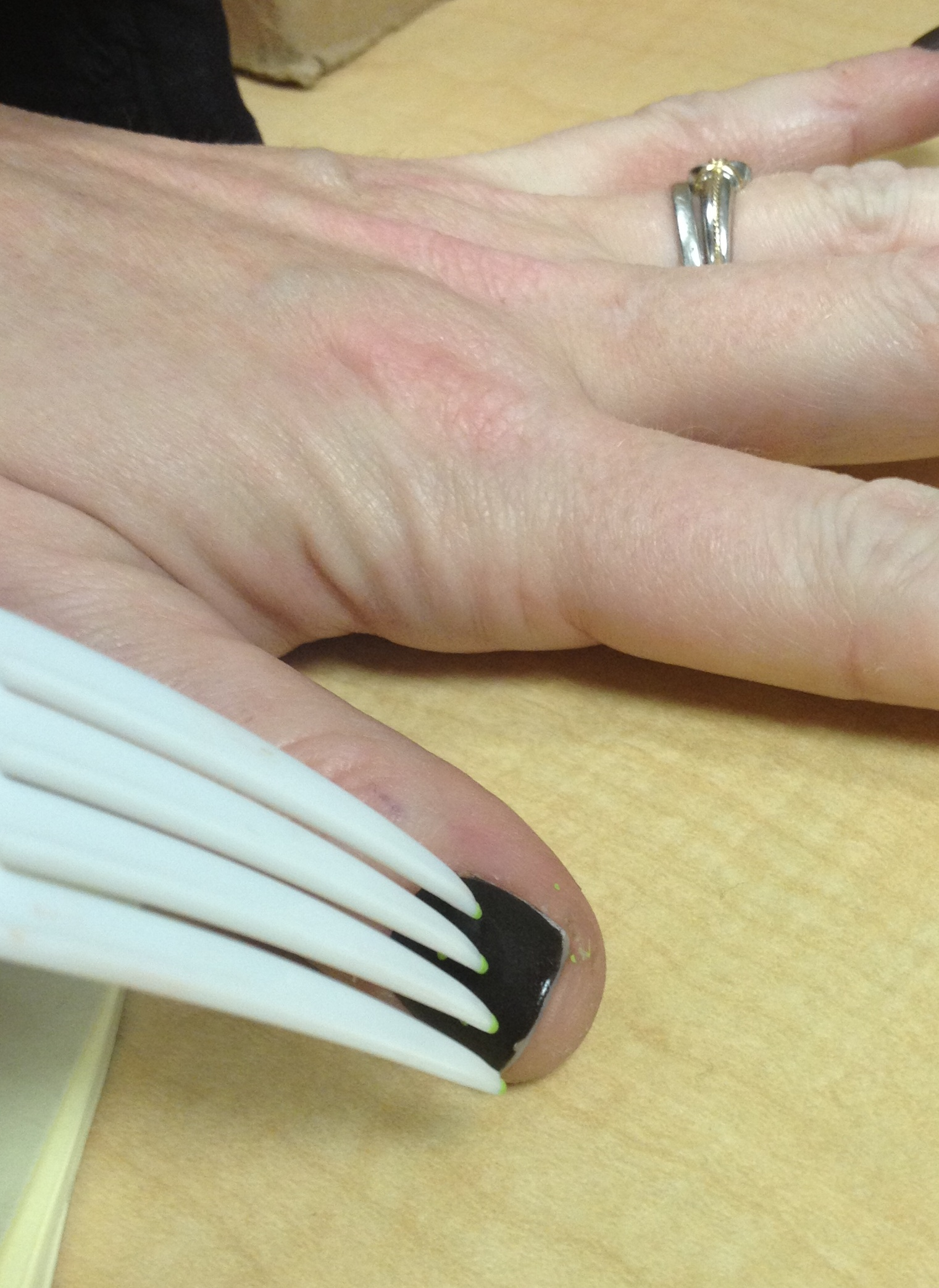 photo of Kym's hand using a plastic fork to put green polka dots on dark nails
