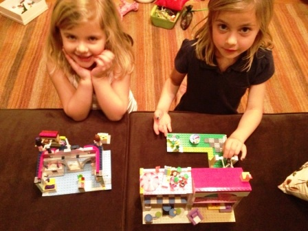 Two young girls playing with Lego Friend sets on a couch with toys in the background