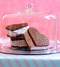 Three heart-shaped ice cream sandwiches, filled with pink ice cream
