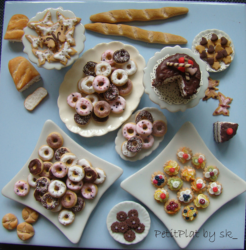 Several plates and platters filled with doughnuts, tarts, cakes, and other baked goods.