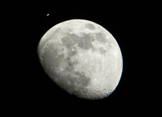 The moon, a few days past the first quarter, with the International Space Station passing by it.