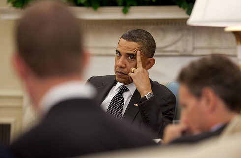 Photo of President Barack Obama in a meeting, looking like he's run out of fucks and resting his hand on his cheek so that his middle finger is extended