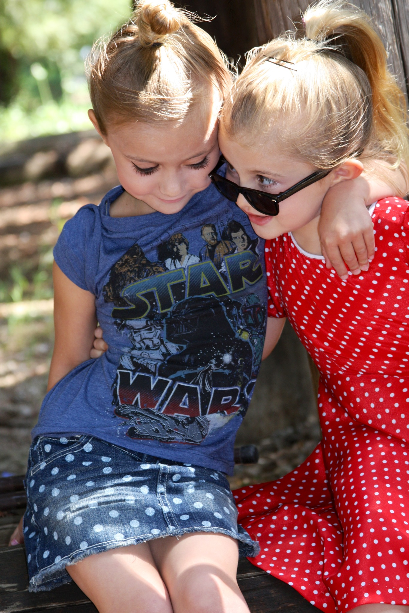 two young girls, Sierra and Charlie, Sierra wearing a blue Star Wars t-shirt and a polka dot denim skirt, cahrlie wearing a red dress and sunglasses