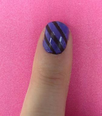 Photo of Kym's nail painted with brown and purple stripes on a pink background