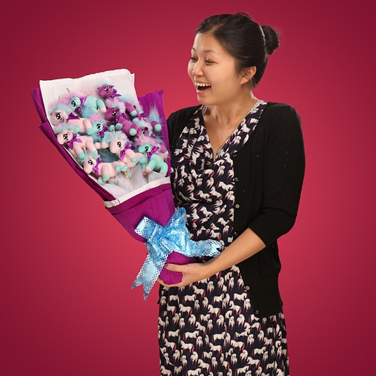 Woman looking happily surprised, holding a bouquet made of 11 plush unicorns