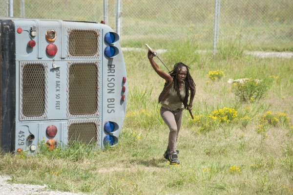 Michonne pulls a sword from the scabbard on her back while walking away from an overturned prison bus
