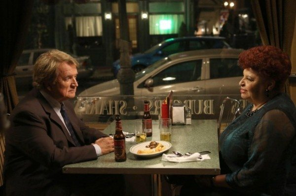 A still from the TV show Bones: the characters of Caroline Julian and Andrew Jursick share a drink