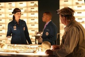 A still from the TV show Bones: the characters of Brennan and Clark Edison investigate a body while being filmed by a guest star.