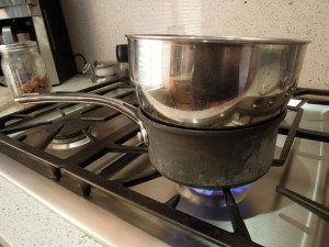 Improvised double boiler, a metal bowl over a saucepan on a gas stove