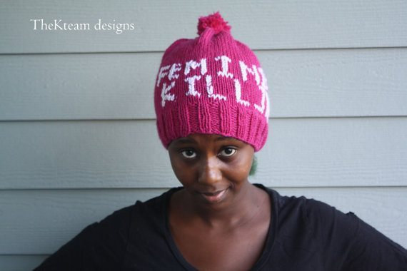 Photo of a young black woman in a black v-neck top wearing a pink knit hat with the words Feminist Killjoy knit in white