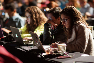 Three people stare at laptops intently in the foreground of a crowd shot. Two of the three are women. Photo credit: JJ Casas www.845a.com
