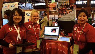 Three women in red shirts stand in front of their table, promoting Froomz.com