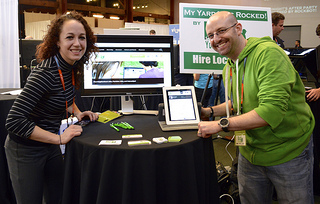 A man and a woman stand in front of a table promoting their product, Rock Your Block